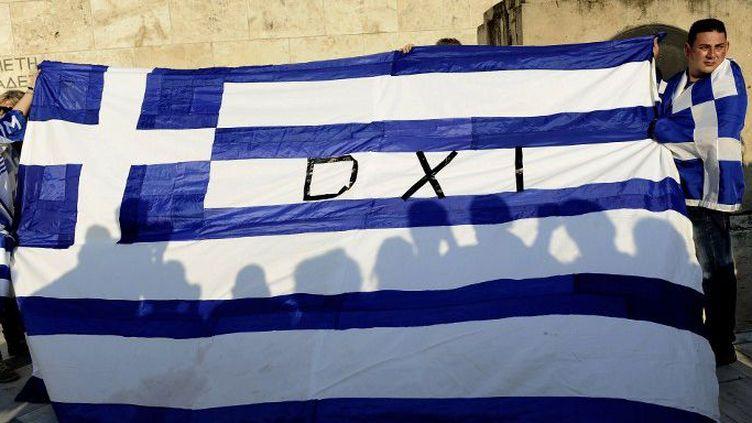 Oxi (non) sur le drapeau grec. Des partisans du «non» au référendum sur le projet d'accord avec la Grèce sur la dette, le 29 juin 2015 à Athènes. (CITIZENSIDE/AGGELIKI KORONAIOU / CITIZENSIDE.COM)