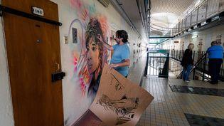 Sur un mur de la prison de Fresnes (Val-de-Marne), l'artiste C215 fait un portrait au pochoir de Juliette Greco (3 juillet 2020) (JOEL SAGET / AFP)