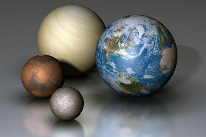 Vue conceptuelle montrant les quatre planètes rocheuses de notre système solaire. La plus grosse est la Terre (D), ensuite vient Vénus (au dernier plan), puis Mars et, au premier plan, Mercure. (MARK GARLICK / MGA / AFP)
