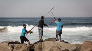 Des pêcheurs sur la populaire plage Blue Lagoon, au nord de Durban,le 17 juillet 2021. (RAJESH JANTILAL / AFP)