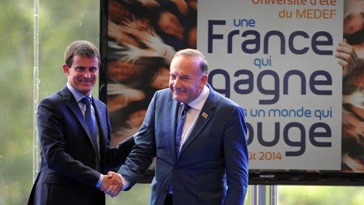 Le président du Medef Pierre Gattaz reçoit Manuel Valls à l'université d'été du Medef àJouy-en-Josas (Yvelines), le 27 août 2014 (ERIC PIERMONT / AFP)