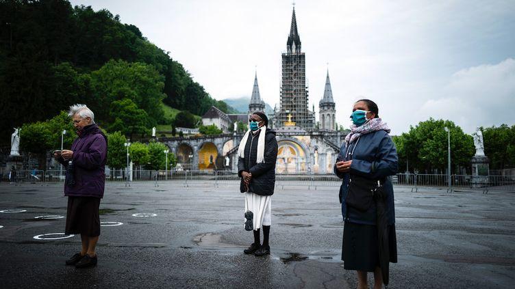 Des pèlerins se recueillent devant la basiliqueNotre-Dame-du-Rosaire, à Lourdes (Pyrénées-Orientales), samedi 16 mai 2020, jour de la réouverture partielle du plus grand centre de pèlerinage catholique de France. (LIONEL BONAVENTURE / AFP)