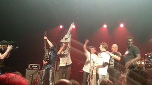 A la fin du concert de soutien vendredi 21 avril à La Souterraine, les ouvriers de GM&S ont remis une guitare en métal au groupe Trust. (AUDREY TYSON / RADIO FRANCE)