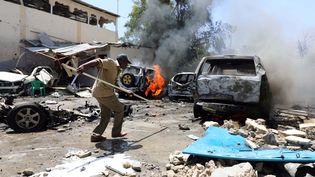 Un Somalien, muni d'une barre de fer, s'apprête à fouiller sous une voiture sur les lieux où une voiture piégée a explosé devant un restaurant à Mogadiscio (Somalie), le 29 janvier 2019.  (FEISAL OMAR / X02643)
