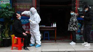 Des personnes font la queue pendant qu'unsoignantprélève un échantillon sur une personne pour dépister le coronavirus Covid-19 à Wuhan, dans la province du Hubei en Chine, le 29 mars 2020 (photo d'illustration). (HECTOR RETAMAL / AFP)