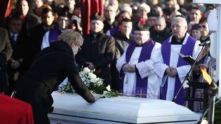 La veuve deLukasz Urban, le camionneur polonais tué avant l'attaque au camion-bélier sur le marché de Noël à Berlin, s'incline sur le cercueil de son mari, le 30 décembre 2016, à Banie, en Pologne. (ODD ANDERSEN / AFP)