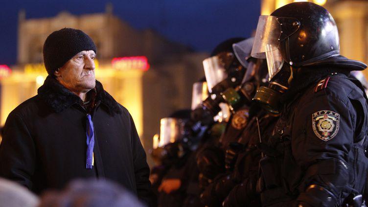 Des policiers ukrainiens font face à un manifestant pro-Europe, le 29 novembre 2013, sur la place de l'Indépendance à Kiev (Ukraine). (VASILY FEDOSENKO / REUTERS)