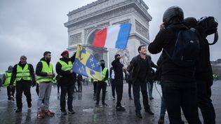 """Une équipe de journalistes filme des """"gilets jaunes"""" devant l'Arc de triomphe, à Paris, le 1er décembre 2018. (NICOLAS CORTES  / HANS LUCAS / AFP)"""