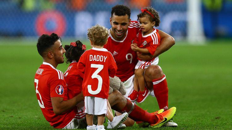 Les joueurs gallois Neil Taylor et Hal Robson-Kanu avec leurs enfants sur la pelouse du stade Pierre Mauroy de Lille, après leur victoire contre la Belgique, le 1er juillet 2016. (KIERAN MCMANUS / AFP)