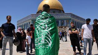 Un Palestinien avec le drapeau du mouvement islamiste Hamas après la prière du vendredi dans l'enceinte de la mosquée al-Aqsa à Jérusalem, le 14 mai 2021. Photo d'illustration. (AHMAD GHARABLI / AFP)