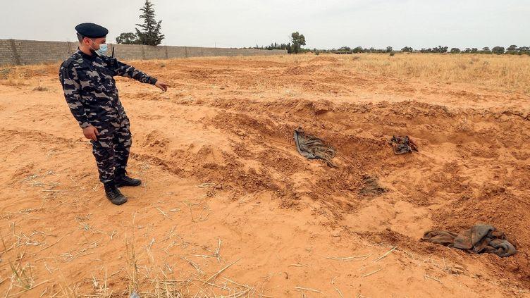 Un membre desforces loyales au Gouvernement d'union national (GNA) montre, le 11 juin 2020, l'endroit au moins huit charniers ont été découverts, près deTarhouna (Libye). (MAHMUD TURKIA / AFP)