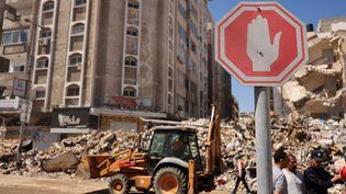 Des ouvriers déblaient une route détruite par les bombardements, à Gaza, le 18 mai 2021. (MOHAMMED ABED / AFP)