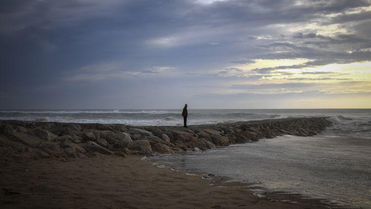 Un homme observe les vagues à Costa da Caparica, à Almada (Portugal), le 13 octobre 2018. (PATRICIA DE MELO MOREIRA / AFP)