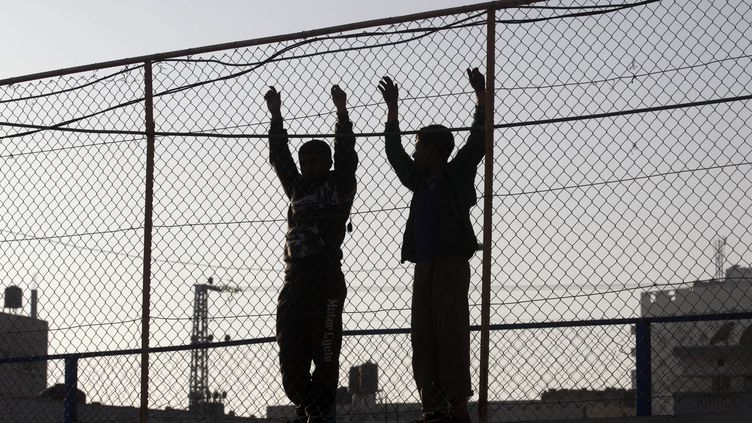 Des garçons palestiniens se tiennent derrière une clôture d'observation lors d'un rassemblement anti-israélien le 26 février 2016 dans la ville de Rafah, dans le sud de la bande de Gaza. (SAID KHATIB / AFP)