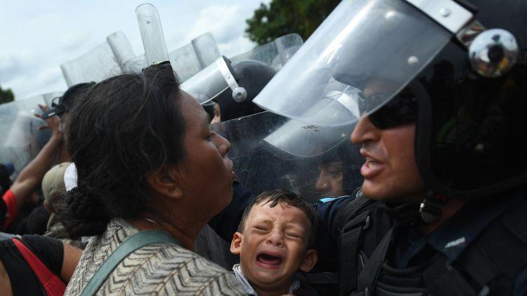 Des policiers empêchentdes réfugiés honduriens de pénétrer sur le territoire mexicain, le 19 octobre 2018 à Ciudad Hidalgo (Mexique). (PEDRO PARDO / AFP)