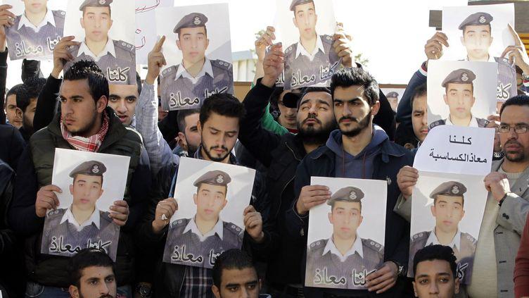 Des manifestants tiennent des portraits du pilote jordanien assassiné par l'Etat islamique, lors d'une manifestation à Amman (Jordanie), mardi 3 février 2015. (KHALIL MAZRAAWI / AFP)