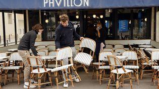 Des salariésmettenten place une terrasse à Paris, le 17 mai 2021. (LUDOVIC MARIN / AFP)