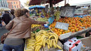 Une cliente s'empare de son sac d'achat sur un stand de fruits et légumes, le 20 novembre 2011 sur un marché à Lille. (PHILIPPE HUGUEN / AFP)