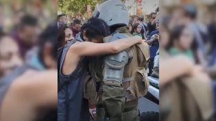 A Santiago (Chili), une manifestante a enlacé un gendarme le 21 octobre 2019. (JUAN ATENAS OROSTICA VIA STORYFUL)