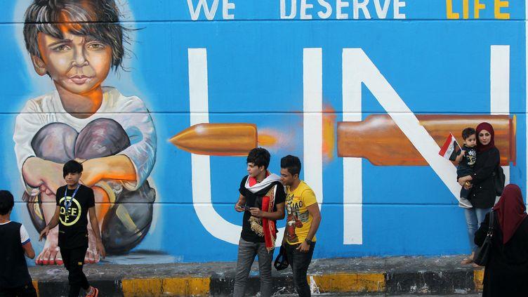 Des Irakiens devant une peinture murale, place Tahrir à Bagdad, le 8 novembre 2019. (AHMAD AL-RUBAYE / AFP)