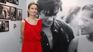 Sarah Biasini, la fille de Romy Schneider, pose devant une photographie de sa mère aux côtés de l'acteur frnaçais Alain Delon, dans le cadre d'une exposition organisée à Cannes en 2012.  (VALERY HACHE / AFP)
