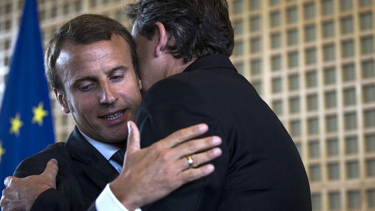 Arnaud Montebourg étreint son successeur Emmanuel Macron au ministère de l'Economie, le 27 août 2014, à Paris. (  MAXPPP)