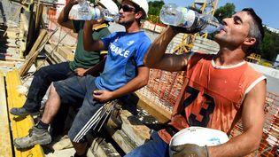 Des ouvriers se désaltèrent sur un chantier de BTP (THIERRY BORDAS / MAXPPP)