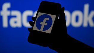 Le logo de Facebook s'affiche sur un téléphone, le 7 avril 2021. (OLIVIER DOULIERY / AFP)