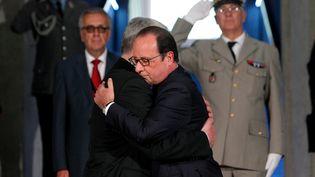 Les présidents français et allemand, François Hollande (D.)et Joachim Gauck se donnent l'accolade, lors ducentenaire du début de la première guerre mondiale sur le site du Hartmannswillerkopf (Haut-Rhin), le 3 août 2014. (THIBAULT CAMUS / AFP)