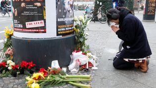 Une femme prie près du marché de Noël à Berlin (Allemagne) où une attaque au camion a fait 12 morts, ce lundi 19 décembre 2016. (? PAWEL KOPCZYNSKI / REUTERS / X00616)
