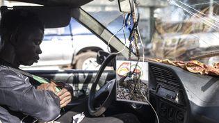 Un homme dans sa voiture avec une photo du colonel Mamady Doumbouya accrochée au rétroviseur, à Conakry, le 13 septembre 2021. Le 5 septembre 2021, les forces spéciales du colonel Mamady Doumbouya ont renversé le président guinéen Alpha Condé. (JOHN WESSELS / AFP)