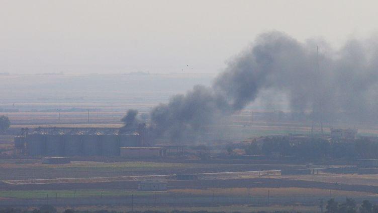 De la fumée s'échappe de bâtiments près de la ville de Ras Al-Aïn, le 18 octobre 2019, en Syrie. (STOYAN NENOV / REUTERS)