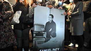 Des proches et collègues, tiennent une photo du professeur assassiné, Samuel Paty, lors de la marche blanche organisée, le 20 octobre 2020, à Conflans-Sainte-Honorine (Yvelines). (BERTRAND GUAY/AFP)