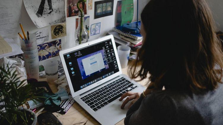 Une élève s'apprête à suivre un cours en visioconférence sur son ordinateur portable,le 19 novembre 2020 à Paris. (JEANNE FOURNEAU / HANS LUCAS / AFP)