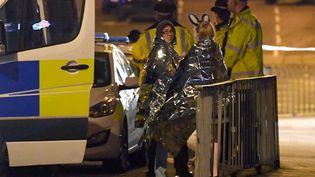Des spectactrices présentes au concert d'Ariana Grande sont prises en charge par les secours, dans la nuit du 22 mai 2017, à Manchester (Royaume-Uni). (PAUL ELLIS / AFP)
