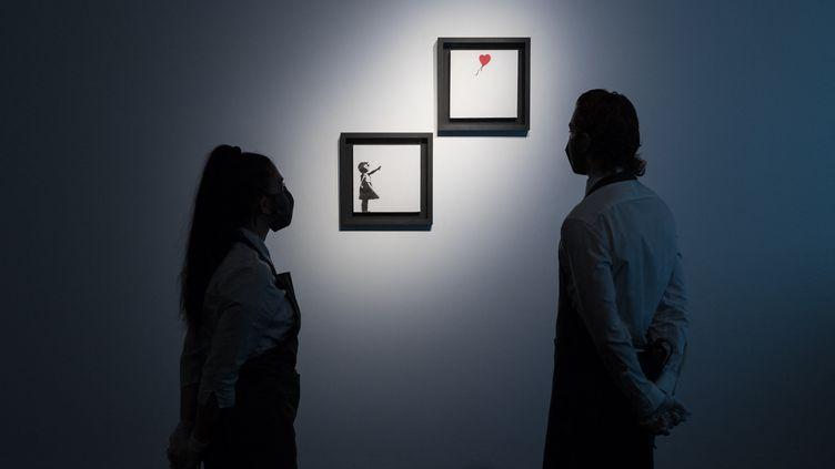 """""""La fille au ballon"""" en diptyque de Banksy (2005) présentée à la presse, le 1er octobre 2021. (WIKTOR SZYMANOWICZ / ANADOLU AGENCY)"""