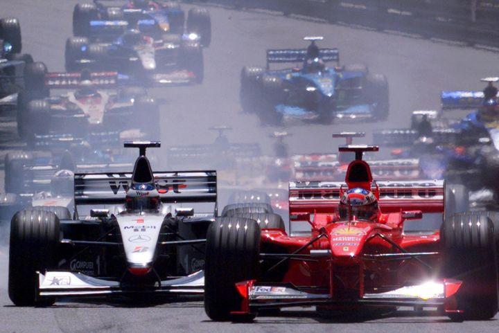 Michael Schumacher (Ferrari) et Mika Häkkinen (McLaren-Mercedes) à la lutte pour prendre les commandes du Grand Prix de Monaco, le 16 mai 1999. (PATRICK HERTZOG / AFP)