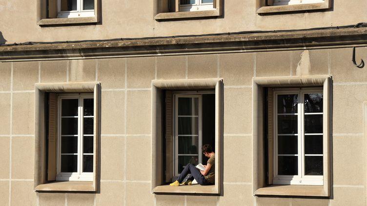 Un étudiant installé sur le rebord de sa fenêtre, à Valence (Drôme), pendant le confinement. (FRANCE BLEU DRÔME-ARDÈCHE)