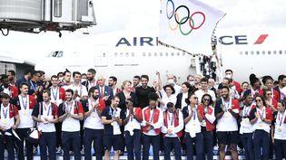 Lamaire de Paris, Anne Hidalgo,avec le drapeau olympique, Tony Estanguet (au centre) et des médaillés à leur retour de Tokyo, le 9 août 2021, à l'aéroport Charles-de-Gaulle. (STEPHANE DE SAKUTIN / AFP)