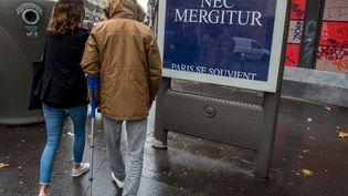 """""""Paris se souvient"""", le 13 novembre 2016.Une victime des attentats passe devant l'affiche qui porte la devise de Paris : 'Fluctuat Nec Mergitur' 'Ilest battu par les flots mais ne sombre pas'. (Illustration) (ROBERT DEYRAIL / GAMMA-RAPHO / GETTY IMAGES)"""