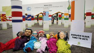 Des militants d'Oxfam portent des masques des chefs d'Etat des pays richeslors d'unemanifestation au cours de la COP21, au Bourget, le 10 décembre 2015. (CHRISTOPHE ENA / AP / SIPA)
