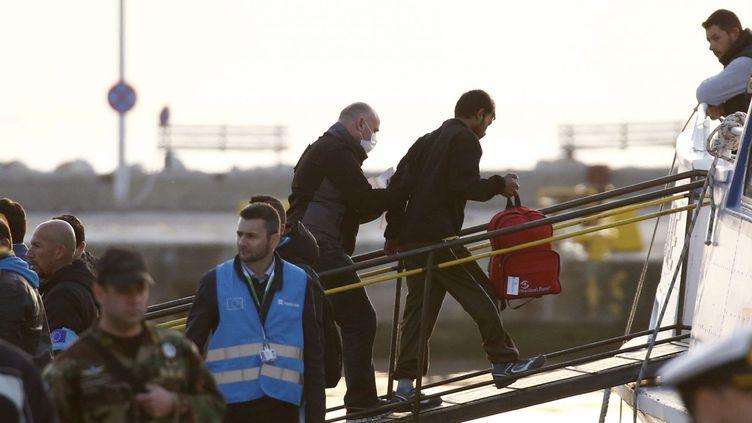 Un agent de Frontex raccompagne un migrant sur un bâteau turc, le 4 avril 2016 sur l'île grecque de Lesbos. (REUTERS/Giorgos Moutafis)
