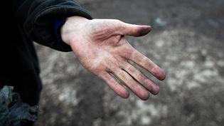 La main couverte de poussière noire d'un agriculteur, àSaint Martin-du-Vivier, près de Rouen (Seine-Maritime), le 30 septembre 2019, après l'incendie de l'usine Lubrizol. (LOU BENOIST / AFP)