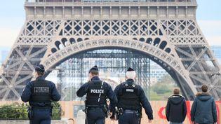 Des policiers patrouillent près de la tour Eiffel, à Paris, le 31 octobre 2020. (ALAATTIN DOGRU / ANADOLU AGENCY / AFP)
