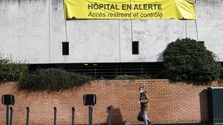 """Un passant devantla façade de l'hôpital de Dunkerque où une banderole indique """"hôpital en alerte"""", le 17 février 2021. (DENIS CHARLET / AFP)"""