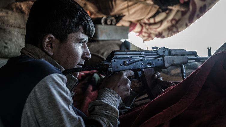 Un combattant kurde défend la ville de Kobani (Syrie), le 26 décembre 2014. (JONATHAN RAA / NURPHOTO / AFP)