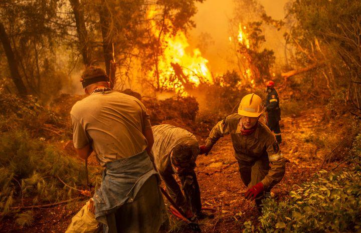 Les pompiers et les volontaires utilisent un tuyau d'arrosagepour tenter d'éteindre un incendie dans le village de Glatsona, sur l'île d'Eubée (Eubée), le 9 août 2021. (ANGELOS TZORTZINIS / AFP)
