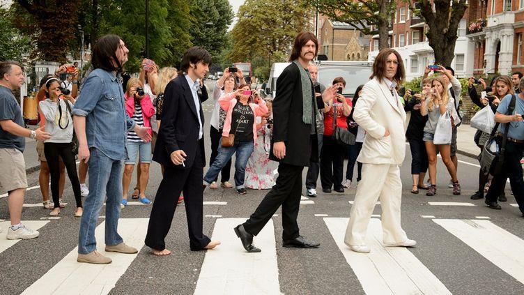 """Des artistes de la comédie musicale """"Let it be"""" posent sur le fameux passage d'Abbey Road le 8 août 2014, jour du 45e anniversaire de la fameuse séance photo des Beatles... et provoquent un embouteillage dans la rue.  (Leon Neal / AFP)"""