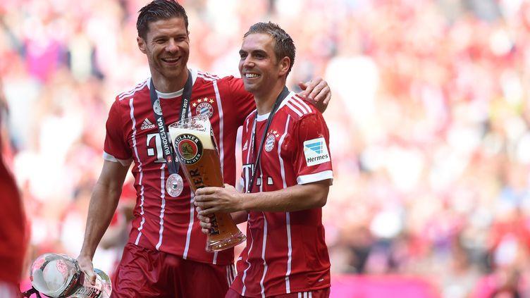 Les joueurs du Bayern Munich Philipp Lahm et Xabi Alonsocélèbrent avec une bière leur victoire contreleSC Fribourg, le 20 mai 2017, à Munich en Allemagne. (CHRISTOF STACHE / AFP)