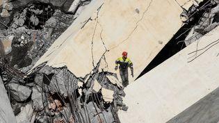 Un sauveteur italien explore les décombres du pont Morandi, à Gênes, le 14 août 2018. (VALERY HACHE / AFP)